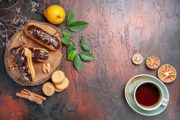 Bovenaanzicht heerlijke choco eclairs met kopje thee op donkere tafel dessert zoete cake