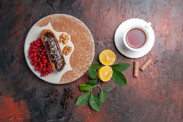 Bovenaanzicht heerlijke choco eclairs met kopje thee op donkere tafel taart dessert cake zoet