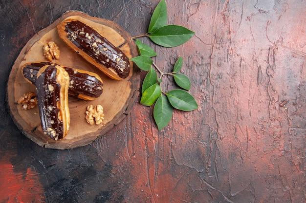 Bovenaanzicht heerlijke choco eclairs op donkere tafel taart zoet dessert
