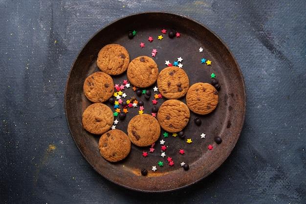Bovenaanzicht heerlijke chocoladekoekjes in bruine ronde plaat op de donkere achtergrond koekjeskoekje zoete thee bakken