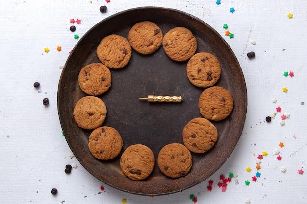 Bovenaanzicht heerlijke chocoladekoekjes in bruine ronde plaat op de witte achtergrond cookie koekje suiker zoet