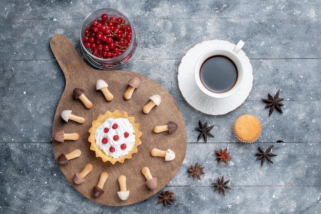 Bovenaanzicht heerlijke chocoladekoekjes met cake van rode veenbessen en kopje koffie op het grijze rustieke bureau
