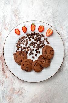 Bovenaanzicht heerlijke chocoladekoekjes met chocoladeschilfers op wit oppervlak koekje suiker zoet bak cakekoekje