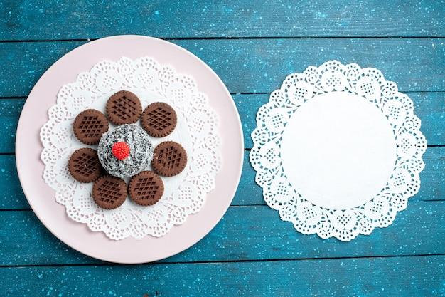 Bovenaanzicht heerlijke chocoladekoekjes met chocoladetaart op blauwe rustieke bureau koekje theekoekje zoete cake suiker