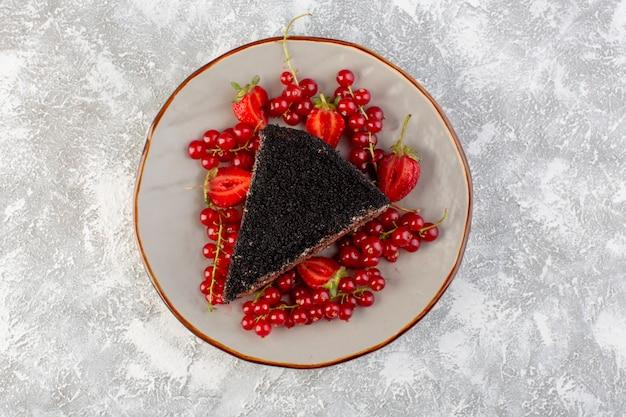 Bovenaanzicht heerlijke chocoladetaart gesneden met choco-room en verse rode veenbessen op de grijze achtergrond cake koekjesdeeg zoet