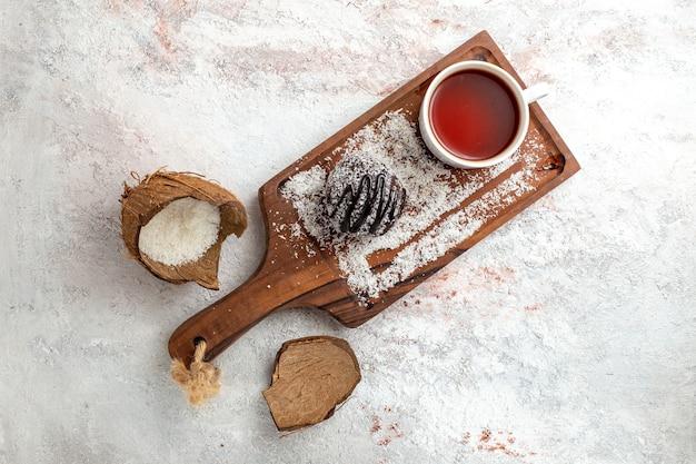 Bovenaanzicht heerlijke chocoladetaart met kopje thee op de lichte witte achtergrond chocoladetaart koekje suiker zoete koekjes thee