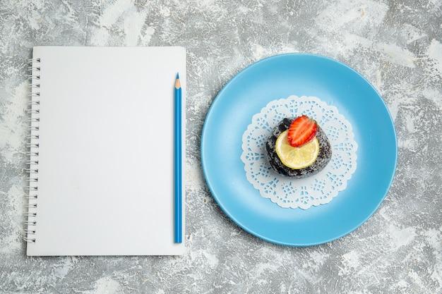 Bovenaanzicht heerlijke chocoladetaart met suikerglazuur en kladblok op de witte achtergrond chocolade suiker koekje zoete cake cookie
