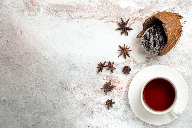 Bovenaanzicht heerlijke chocoladetaart met thee op de lichte witte achtergrond chocoladetaart koekje suiker zoete koekjesthee