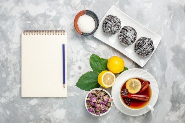Bovenaanzicht heerlijke chocoladetaarten met citroen en kopje thee op het lichtwitte oppervlak fruitcake koekje zoete suiker bak koekje