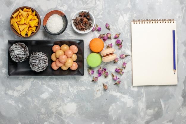 Bovenaanzicht heerlijke chocoladetaarten met crackers en macarons op lichtwit bureaukoekje bak cake zoet suikerkoekje