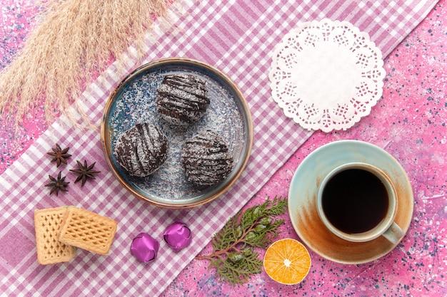 Bovenaanzicht heerlijke chocoladetaarten met kopje thee en wafels op roze