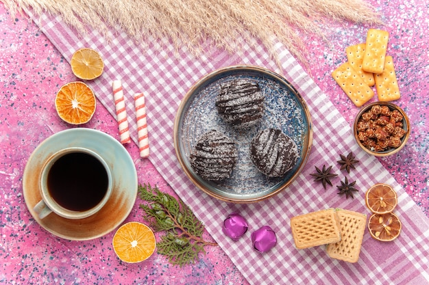 Bovenaanzicht heerlijke chocoladetaarten met thee en wafels op roze