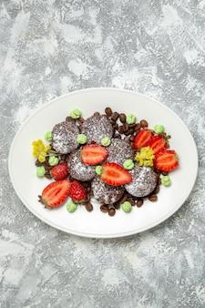 Bovenaanzicht heerlijke chocoladetaarten met verse aardbeien op witte oppervlakte koekje suikertaart zoete thee koekje