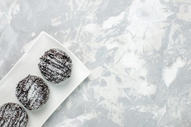 Bovenaanzicht heerlijke chocoladetaarten met witte poedersuiker op het lichtwitte oppervlak cakekoekje bak chocolade zoete suikerthee