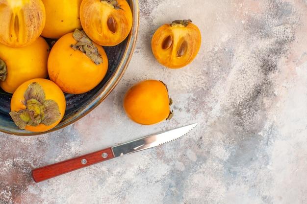 Bovenaanzicht heerlijke dadelpruimen in een kom persimmon en mes op naakte achtergrond