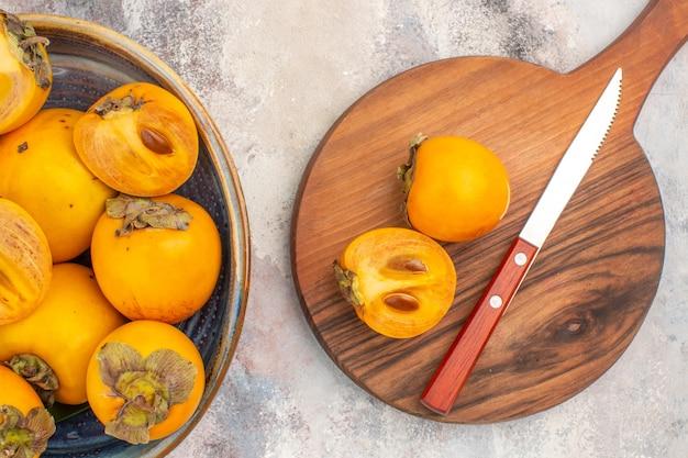 Bovenaanzicht heerlijke dadelpruimen in een kom persimmon en mes op snijplank op naakte achtergrond