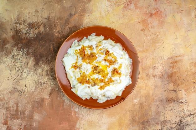 Bovenaanzicht heerlijke deegplakken met yoghurt en olie op lichte ondergrond