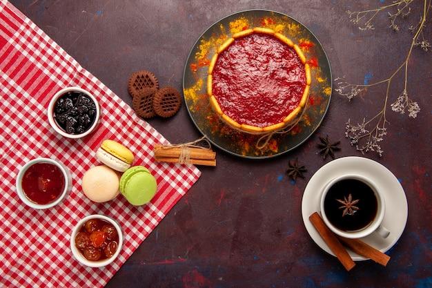 Bovenaanzicht heerlijke dessertcake met kopje koffie en fruitjams op donker bureau koekje suiker koekjescake dessert zoet