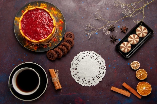 Bovenaanzicht heerlijke dessertcake met kopje koffie en koekjes op donker bureau koekje suiker koekjes cake dessert zoet