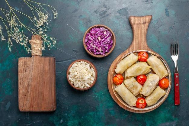 Bovenaanzicht heerlijke dolma vleesmaaltijd gerold met kool en tomaten op donkerblauwe achtergrond vlees eten diner groenten schotel koken