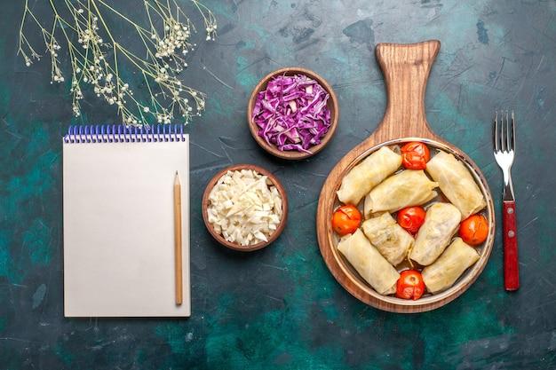 Bovenaanzicht heerlijke dolma vleesmaaltijd gerold met kool en tomaten op het donkerblauwe bureau vlees eten diner groenten schotel koken