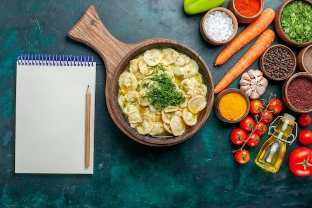Bovenaanzicht heerlijke dumplings met groenten en verschillende smaakmakers op donkergroen oppervlak maaltijd voedselingrediënt product deeg vlees