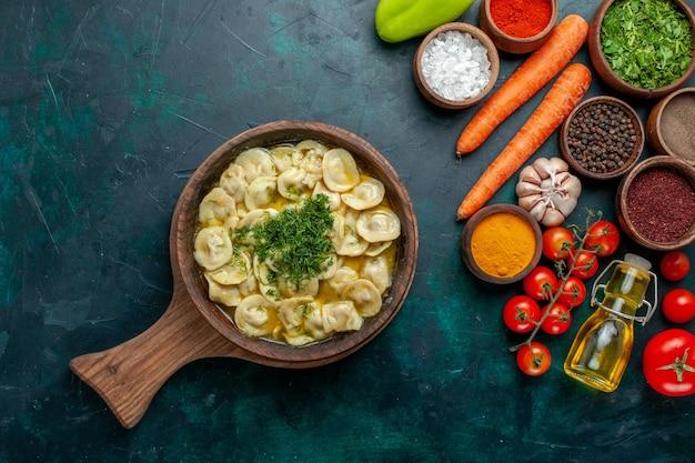 Bovenaanzicht heerlijke dumplings met groenten en verschillende smaakmakers op donkergroene muur maaltijd voedselingrediënten product deeg vlees