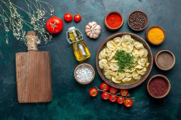 Bovenaanzicht heerlijke dumplings met verschillende kruiden op donkergroen oppervlak maaltijd deeg vlees groenten diner gebak
