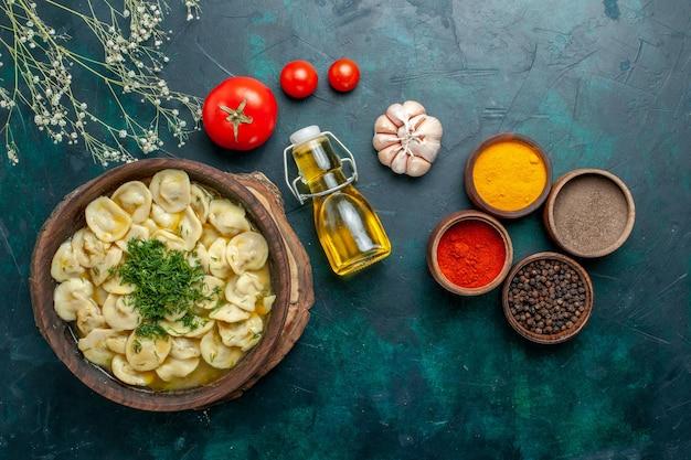 Bovenaanzicht heerlijke dumplings met verschillende kruiden op donkergroene muur maaltijd deeg vlees groente diner gebak