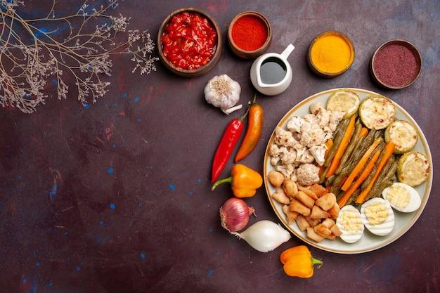 Bovenaanzicht heerlijke eiermaaltijd met gekookte groenten en kruiden op donkere ruimte