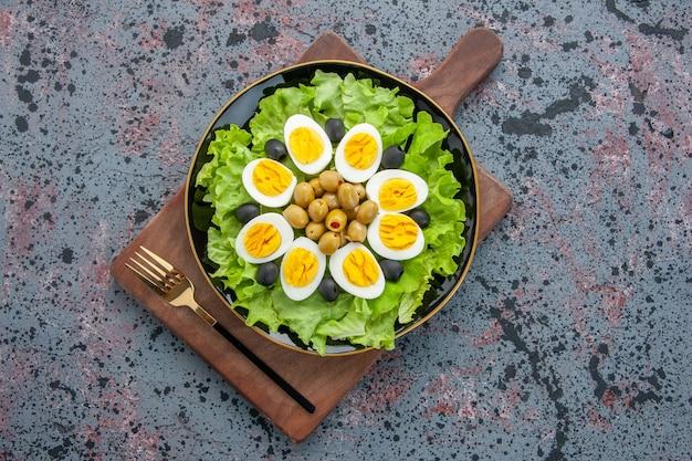 Bovenaanzicht heerlijke eiersalade groene salade en olijven op lichte achtergrond