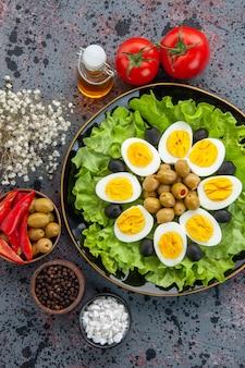 Bovenaanzicht heerlijke eiersalade met tomaten en olijven op lichte achtergrond