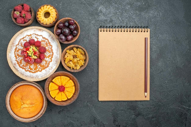 Bovenaanzicht heerlijke frambozencake met fruit en rozijnen op een grijze achtergrond, zoete caketaart, fruitbessenkoekje