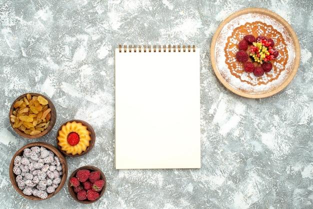 Bovenaanzicht heerlijke frambozencake met rozijnen en snoepjes op witte achtergrondcake, zoete taartkoekjes