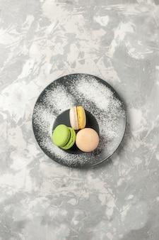 Bovenaanzicht heerlijke franse macarons in plaat op het witte oppervlak cake koekje suiker bakken zoete taart