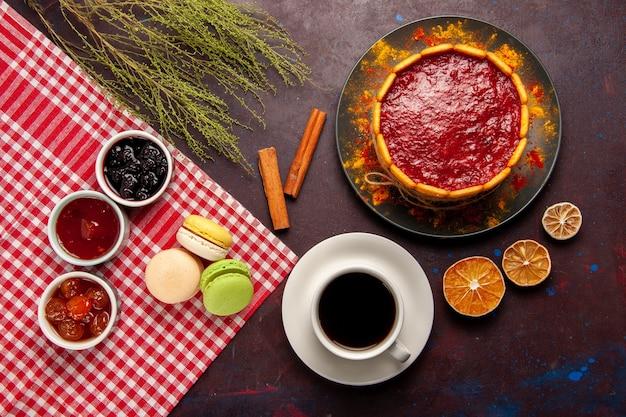 Bovenaanzicht heerlijke franse macarons met fruitjam en kopje koffie op donker bureau zoet fruit marmelade cake koekje zoete suiker