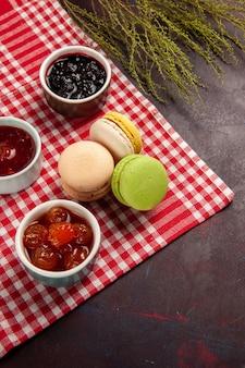 Bovenaanzicht heerlijke franse macarons met fruitjam op het donkere oppervlak zoet fruit marmelade cake koekje zoete suiker