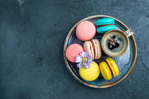 Bovenaanzicht heerlijke franse macarons met koffie op donkere ruimte
