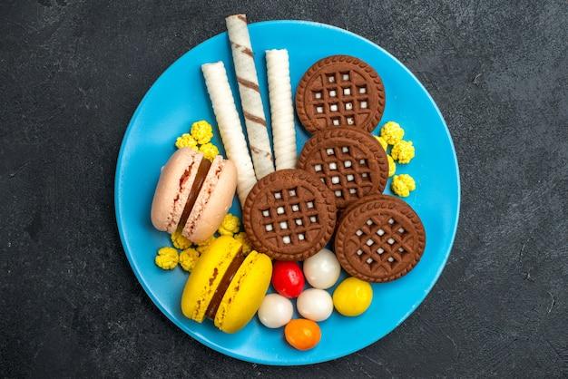 Bovenaanzicht heerlijke franse macarons met snoepjes en chocoladekoekjes op donkergrijs oppervlak biscuit suikertaart zoet bak cookie