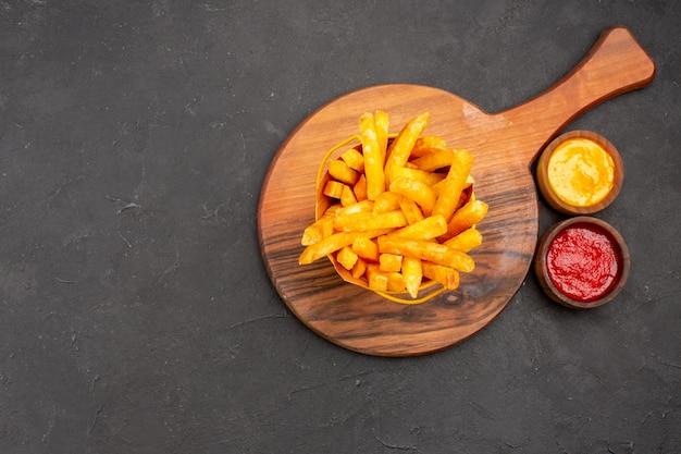 Bovenaanzicht heerlijke frietjes in mand op donkere achtergrond snack hamburger fastfood aardappelmeel