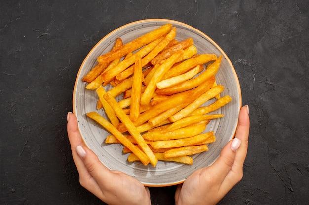 Bovenaanzicht heerlijke frietjes in plaat op de donkere achtergrond aardappelmaaltijd sandwich schotel hamburger fastfood