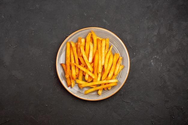 Bovenaanzicht heerlijke frietjes in plaat op donkere achtergrond aardappel hamburger maaltijd sandwich diner schotel