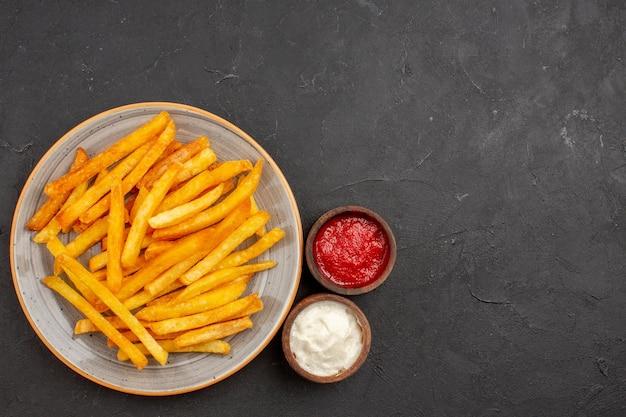 Bovenaanzicht heerlijke frietjes in plaat op donkere achtergrond aardappelen maaltijd sandwich schotel hamburger fastfood