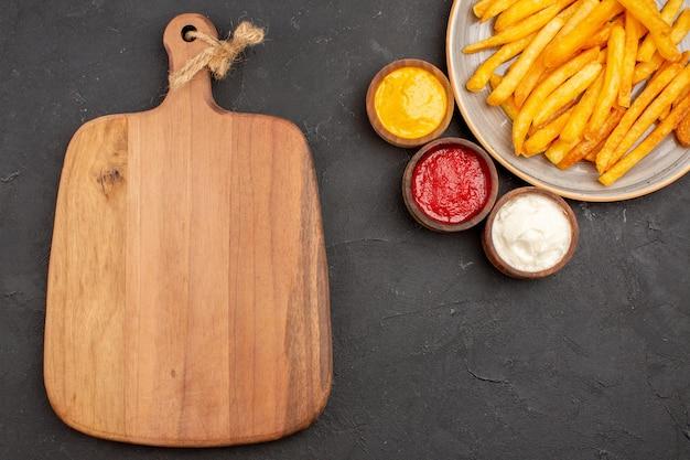 Bovenaanzicht heerlijke frietjes met kruiden op donkere achtergrond schotel aardappelen maaltijd fastfood hamburger