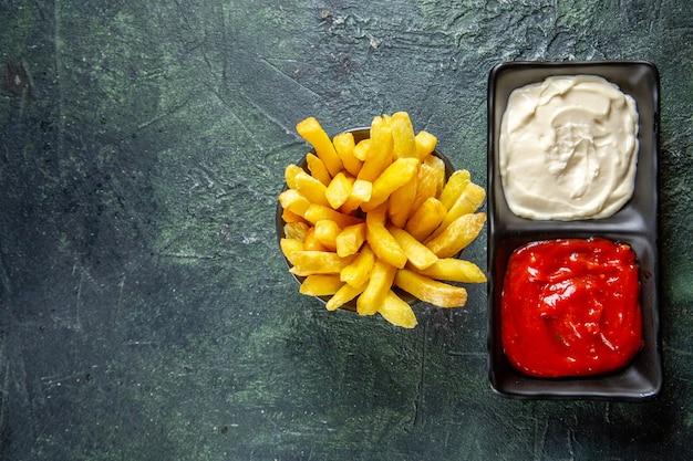 Bovenaanzicht heerlijke frietjes met kruiden op donkere ondergrond
