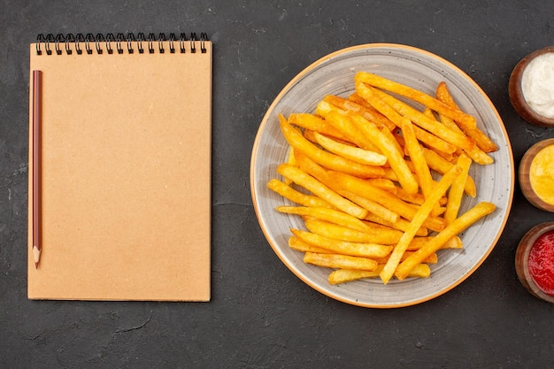 Bovenaanzicht heerlijke frietjes met kruiden op donkere vloer aardappelmeel hamburger fastfood gerecht