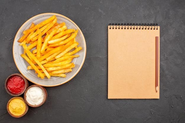 Bovenaanzicht heerlijke frietjes met kruiden op een donkere achtergrond aardappel maaltijdschotel hamburger fastfood fast