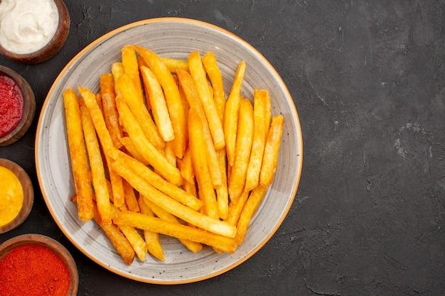 Bovenaanzicht heerlijke frietjes met sauzen op donkere achtergrond fastfood aardappelschotel hamburger maaltijd