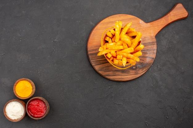 Bovenaanzicht heerlijke frietjes met sauzen op donkere vloerschotel hamburger fastfood aardappelmaaltijd