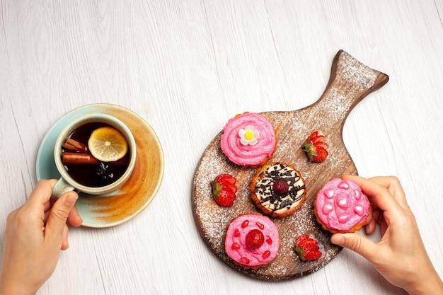 Bovenaanzicht heerlijke fruitcakes romige desserts met fruit en kopje thee op witte achtergrond cream tea zoet dessert cake cookie